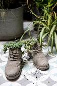 Ein Paar Schuhe als originelle Pflanzgefäße auf Balkon