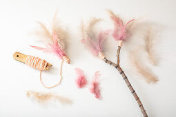 Tying feathers to twig with woollen yarn