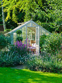 Outdoor living room in greenhouse amongst perennials and shrubs