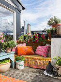 Colourful blanket and cushions on bench on roof terrace