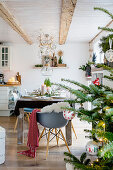 Christmas tree and set dining table in open-plan interior