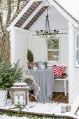 Cosily decorated arbour with deck in wintry garden