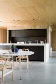 Dining table and designer chairs in front of open-plan kitchen in architect-designed house