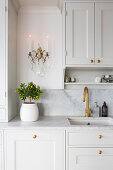 Small citrus tree below sconce lamp in classic kitchen