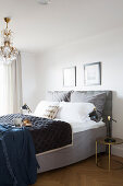 Bed with grey valance and chandelier in elegant, hotel-style bedroom