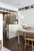 Dining table next to open doorway with half-height partition wall in apartment interior