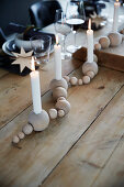 Festively set table decorated with garland of wooden baubles holding candles