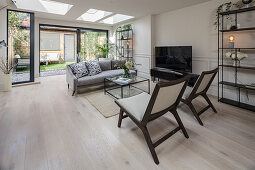 Seating area around TV in living room with skylights and glass wall overlooking garden