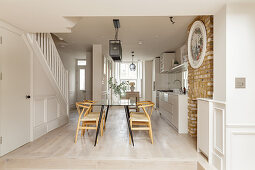 White kitchen and dining area on raised level in elongated, open-plan interior