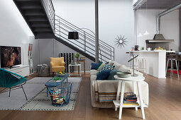 Living room and open-plan kitchen in loft apartment with steel staircase