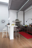 Open-plan stainless steel kitchen with white breakfast bar and steel ceiling in loft apartment