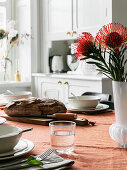 Vase of proteas on table simply set with orange tablecloth