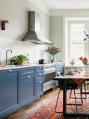 Blue cupboards in cosy kitchen-dining room with dining table on kilim rug