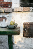 Bowl of grapes on battered green stool in front of old wall