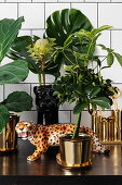Leopard figurine and exotic plants in golden cache pots