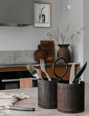 Cutlery in rustic metal containers in kitchen in natural shades