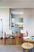 50s chairs with colourful upholstery in front of sliding door leading into kitchen