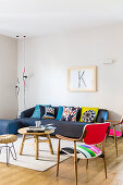 Colourful scatter cushions on dark blue sofa, wooden table, stool and fifties chairs