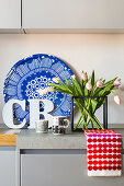 Tray, flowers and tea towel providing colourful accents on grey kitchen counter
