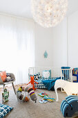 Cot and colourful toys in light-flooded child's bedroom