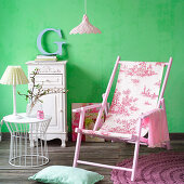 Deck chair with toile-de-jouy fabric seat in front of green wall