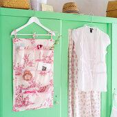 Hand-sewn organiser made from toile-de-jouy fabric hanging on wardrobe