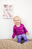 Little girl sitting on sofa back below her painting on wall