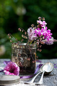 Posy of red campion, plantain flowers and wild grasses in old tea caddy next to petunia flower and spoons on table