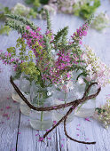 Jars filled with hydrangeas, lady's mantle, and purple loosestrife (Lythrum salicaria)