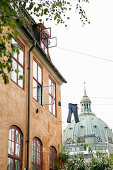 Trousers hung from washing line between period buildings in front of a domes roof in Copenhagen