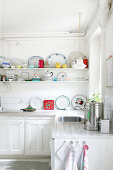 White kitchen-dining room with brightly coloured accents on shelves