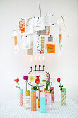 Postcards clipped to Zettel'z lamp over colourful vases holding single flowers