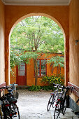 Bicycles in arched passageway leading into summery courtyard