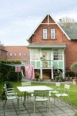 Green garden furniture on terrace in garden of brick house