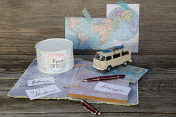 Handmade money box on top of travel journal with maps
