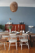 White spoke-back chairs around wooden table in front of blue wall in dining room
