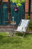 Deckchair wich cushions outside house with petrol-blue wooden doors