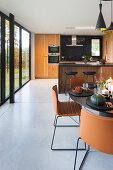 Round dining table and brown chairs in front of open-plan kitchen with glass wall