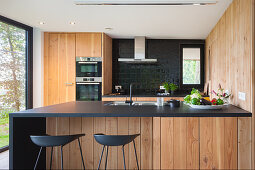 Modern kitchen with black worksurface and wooden fronts