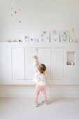 Little girl standing in front of floating cupboards with baby photos on top