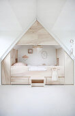 Modern cubby bed surrounded by storage in child's attic bedroom