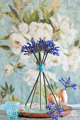 Standing arrangement of blue agapanthus on copper tray