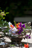 Colourful bouquet of sweet peas and green asparagus in old silver teapot