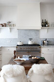 Chairs with fur blankets at table in rustic white kitchen