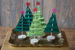 Festive arrangement of handmade paper Christmas trees made from sheet music