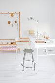 Metallhocker und Stuhl am Schreibtisch auf weißem Dielenboden
