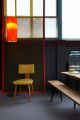 Standard lamp next to yellow chair in dining room with accents of colour