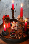 Festive arrangement with red candles and Maneki-neko cat on tray