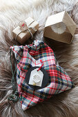 Tartan sachet, gift and paper house on fur rug
