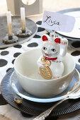 Maneki-neko cat used as holder for name tag on set table